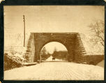 Snow covered road and train underpass, with horse drawn carriage in distance, circa 1900, Morris...