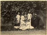 Young men and women in group by vine covered wall, circa 1880