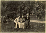 Young men and women posing on bench in garden, circa 1880