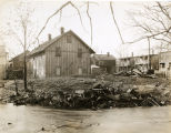 Buildings by edge of water and remnants of car, circa 1920, Morristown, NJ