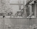 Six people standing behind fence with dog, not dated, Morristown, NJ