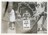 Little girl in carriage with sign saying, in the heart of America, 08/17/26, Newark, NJ